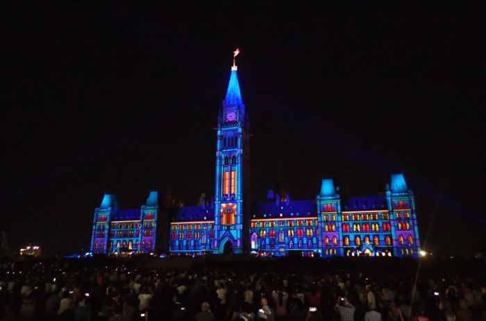 Photo of Centre Block lit up at night.